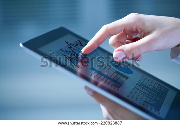 Gros plan sur des mains de femmes touchant une tablette numérique avec un diagramme d'entreprise