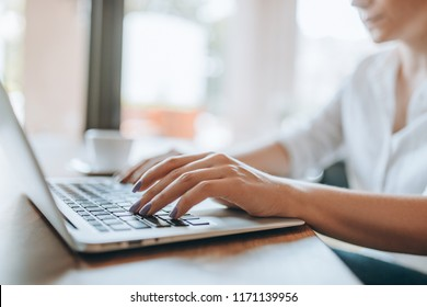 Closeup female hands typing on laptop keyboard. Woman working at home office.