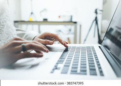 Close-up of female hands typing on the laptop keyboard, woman's hands using laptop in interior, filtered image