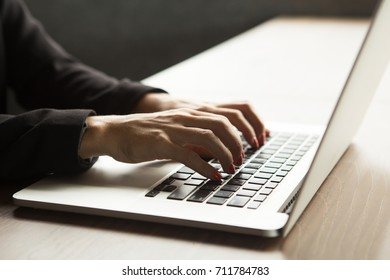 Close-up of female hands typing on laptop at table