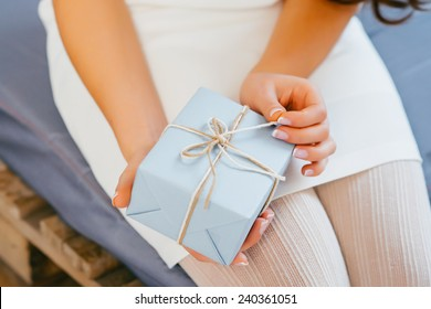 Close-up of female hands unpacking a present.