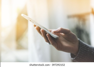 Closeup of female hands using modern smart phone in interior, woman working on cellpone or typing text message, flare light
