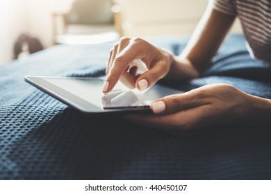 Close-up of female hands using modern digital tablet in home interior, young hipster girl lying in cozy bedroom and typing text message via tablet pc, flare light, film effects