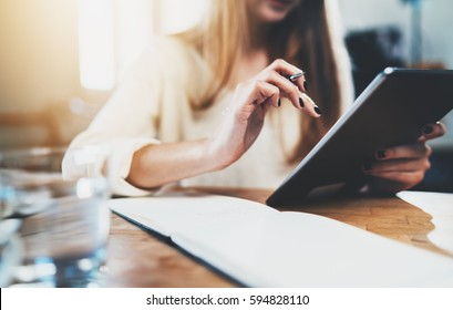 Closeup of female hands using modern digital tablet at vintage loft, young businesswoman with long hair working at office via tablet pc, hipster girl chatting at social network with friends