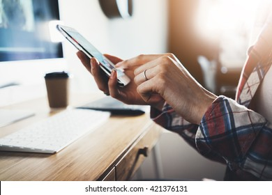Close-up of female hands using smart phone while working on computer at modern office interior, businesswoman typing text message on her cellphone at loft interior, flare light, flare light