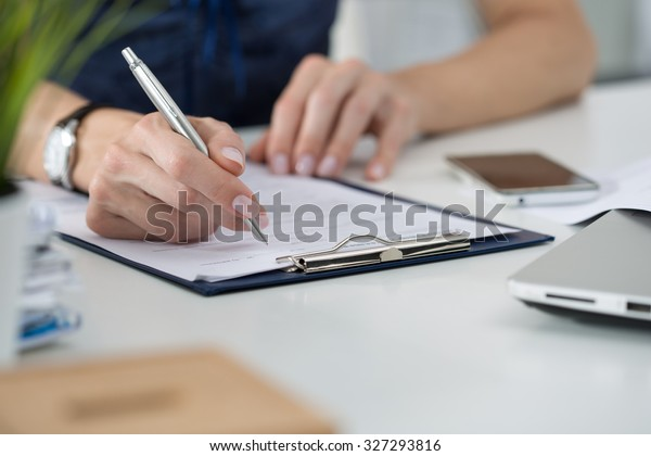 Close-up of female hands. Woman writing something sitting at her office. Signing documents