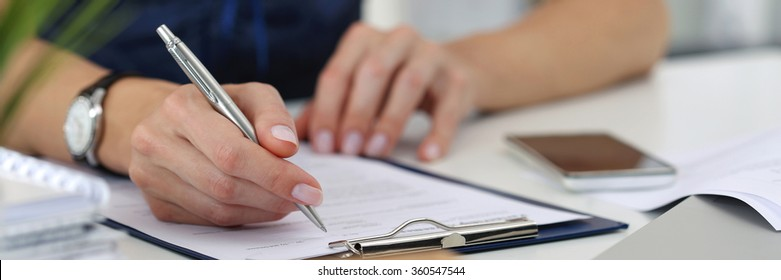 Close-up of female hands. Woman writting something and looking at mobile phone screen sitting at her office. Letter box format