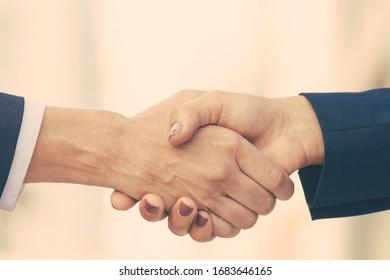 Closeup of female handshake. Business women in office jackets shaking hands. Businesswomen concept