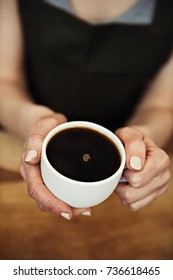Close-up of female holding fresh coffee mug. Concept of coffee break and relaxation.
