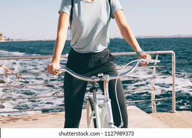 Close-up female holding handlebars of cruiser bike. Young woman wearing casual outfit and backpack sitting at her vintage bicycle at the background of blue sea foamy waves at summes sunny day.