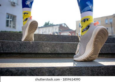 Close-up female legs in blue leggins and yellow socks running upstairs outdoors.