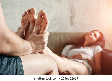 Close-up of female legs receiving a foot massage from her husband. Perfect marriage, good husband, tired wife.