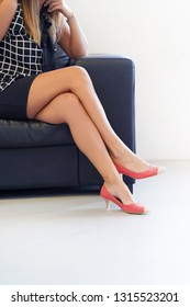 Close-up of female legs in red shoes sitting on a sofa. Woman's legs in red high-heeled shoes, the woman is sitting relaxed on sofa, health and beauty legs concepts. Sexual harassment at work.