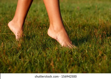 close-up of female legs walking on green grass barefoot