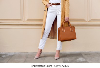 Closeup female legs. Woman in coat and white jeans with brown handbag. Fashion street autumn outfit