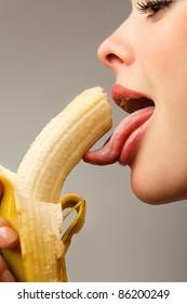 Close-up female mouth licking peeled banana