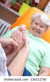closeup of a female Nurse massaging foot of an elderly woman