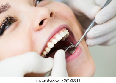 Close-up of female with open mouth during oral checkup at the dentist.Dentist
