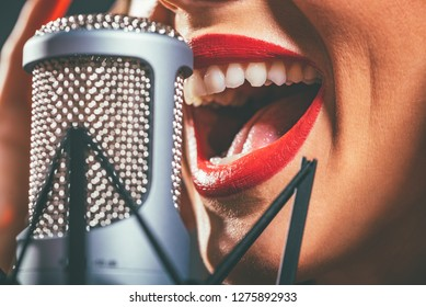 Close-up of a female open mouth with red lipstick singing on the microphone.