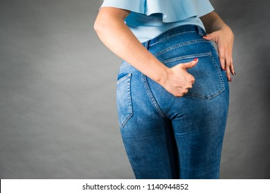 Closeup of female plus size hips buttocks wearing blue jeans, woman presenting fashionable outfit, showing thumb up. Fashion clothing femininity concept. Gray background