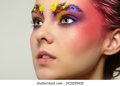 Close-up female portrait with unusual face art make-up. Paint on brows, hair and around eyes.