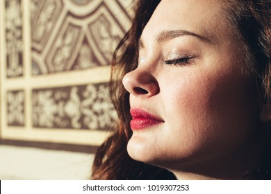 Close-up female portrait. Woman enjoys sun.