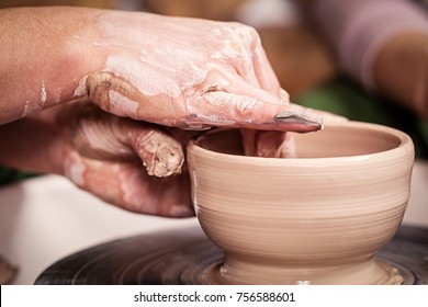 Close-up of a female potter making a bowl of brown clay on a potter's wheel, side view