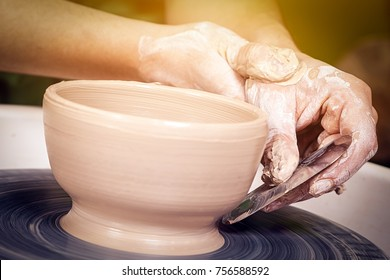 A close-up of a female potter sculpts a bowl of brown clay on a potter's wheel and equates it with a special mettalic cicle tool, a side view