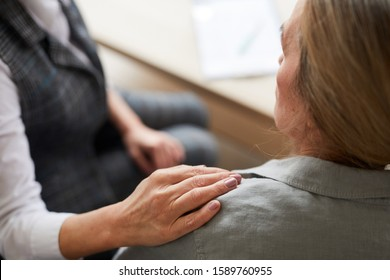 Closeup of female psychologist laying hand on shoulder of senior patient while comforting her during therapy session, copy space