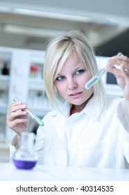 Closeup of a female researcher holding test tubes with chemicals while carrying out some experiments in a laboratory