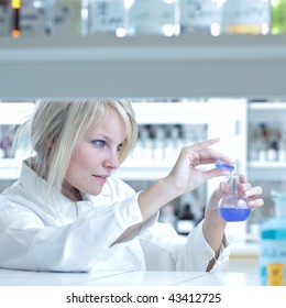 Closeup of a female researcher holding up a test tube and a retort and carrying out some experiments