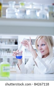 Closeup of a female researcher holding up a test tube and a retort and carrying out experiments