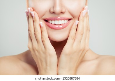 Closeup female smile and manicured hand. French manicure, white teeth and pink glossy lips makeup