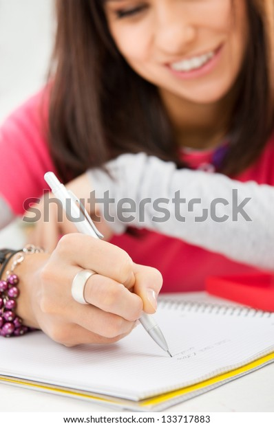 Closeup of female student writing notes