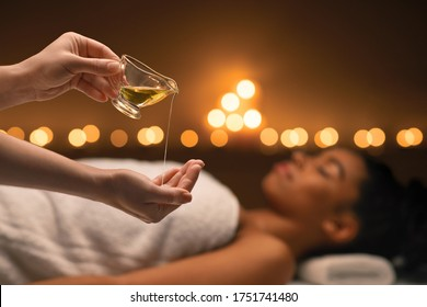 Closeup of female therapist applying massage oil on hands before therapy, young black lady lying on massage table at spa - Shutterstock ID 1751741480
