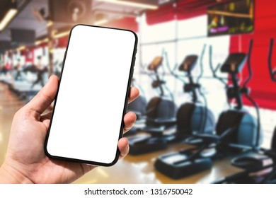 Close-up of female use Hand holding smartphone blurred images touch of Abstract blur of defocused sport gym interior and fitness health club with sports exercise equipment Gym blur background.