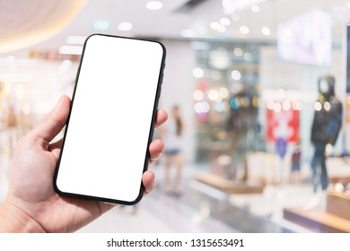 Close-up of female use smartphone blurred images in the mall and Clothes shop blur of the background.