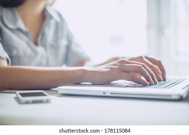 Closeup of a female using a laptop , focus on hands