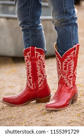 Closeup of female wearing jeans in red cowboy boots standing on a gravel road