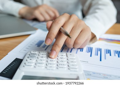 Closeup of female who are using their fingers to press the calculator for calculating bills in the office.finance report. Business office concept.
