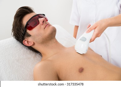 Close-up Of Female Worker Giving Man Laser Epilation On Chest In Salon