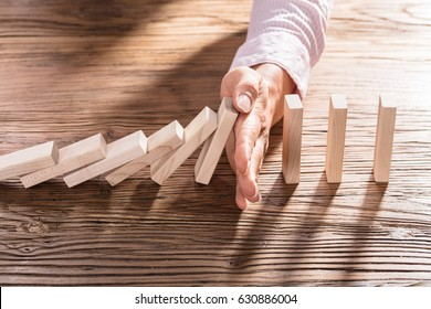 Close-up Of A Female's Hand Stopping The Domino From Falling On Wooden Desk