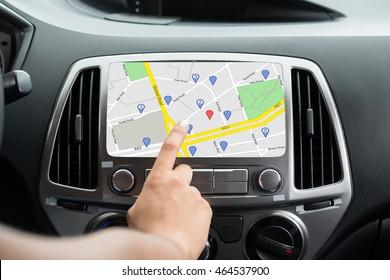 Close-up Of Female's Hand Using GPS Navigation Inside Car