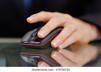 Closeup of a female's hand working on black computer mouse.