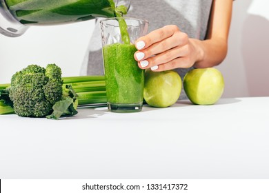 Close-up female's hands with white manicure pouring healthy green smoothie in glass at table near ingredients: apples, broccoli and celery.