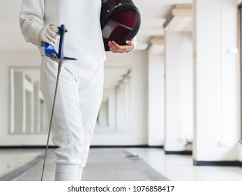 Close-up of a fencer in white fencing suit and holding mask and a sword on gym background. sport concept.