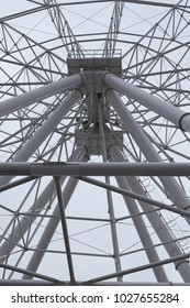 Closeup of a Ferris wheel at an amusement park on a cloudy sky background.