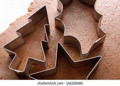 Closeup of festive cookie cutters on gingerbread dough