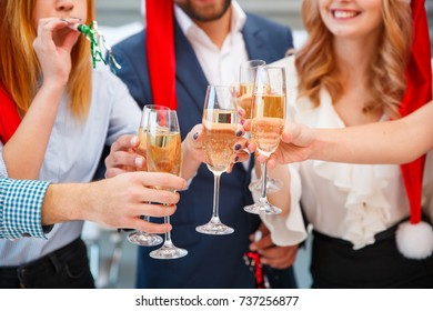 Close-up festive people cheering with drinks on a New Year on a blurred background. Christmas holidays concept.