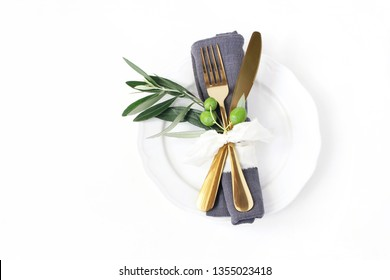 Closeup of festive table summer setting with golden cutlery, olive branch, grey linen napkin, porcelain dinner plate and  silk ribbon on white table background. Mediterranean wedding, restaurant.